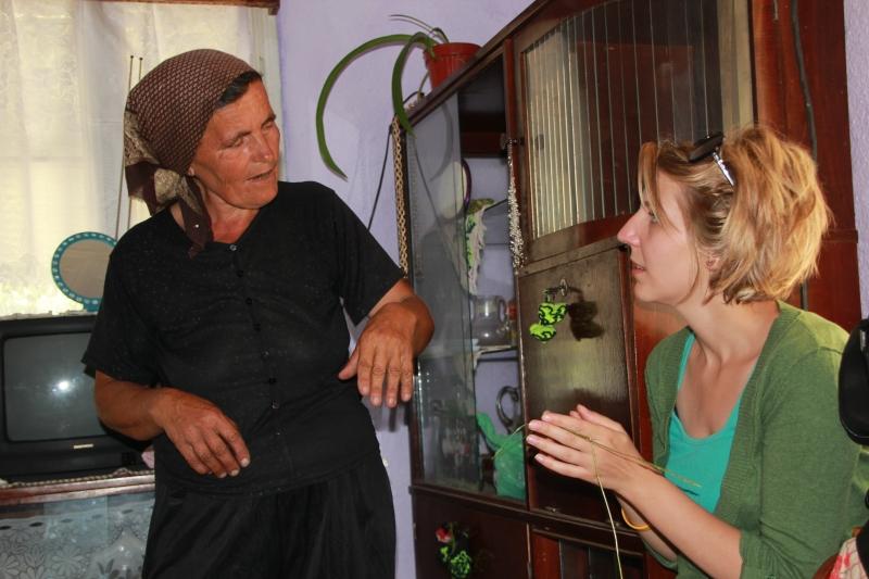 Claudia instructing Laura in bee lore.
