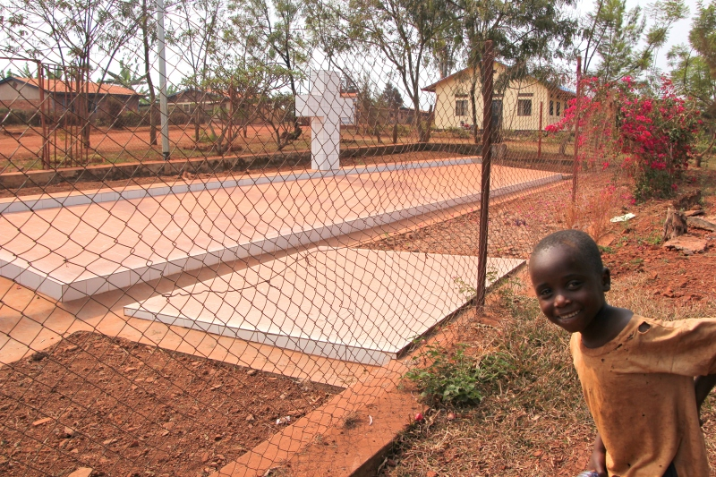 Rwandan boy popping in front of a genocide mass grave in Kigungo, Eastern Province.